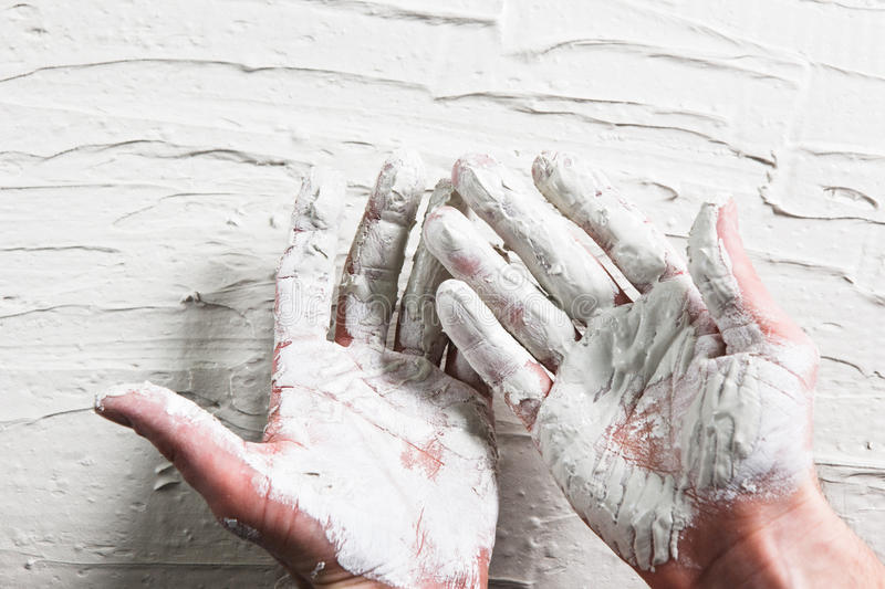 Builder hands in wet white plaster on stucco wall. Builder Hand White Plaster Stucco Wall Worker Flat Lay Construction Repair Concept stock image