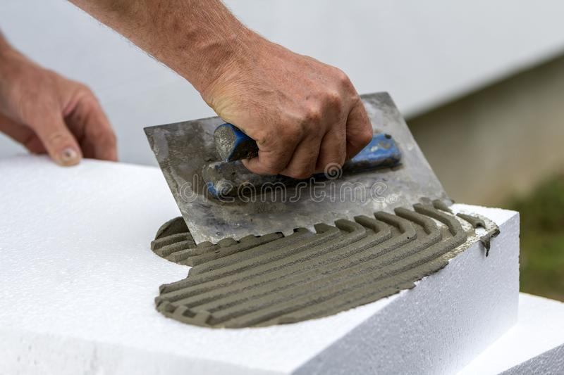 Close-up of worker hand with trowel applying glue on white rigid polyurethane foam sheet for house insulation. Modern technology, royalty free stock image