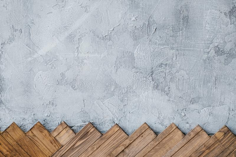 Gray stucco plaster wall background wood planks. Gray stucco plaster wall background. arranged row of wood planks at the bottom royalty free stock images