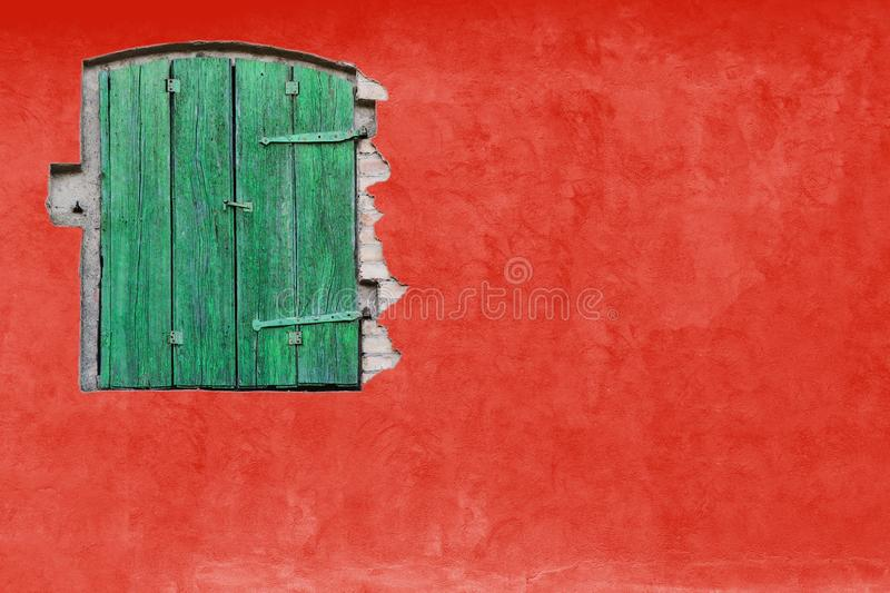 Green window on red stucco wall. Vivid bright red colour house home facade with green wooden window. And large empty red wall texture empty background space royalty free stock photography