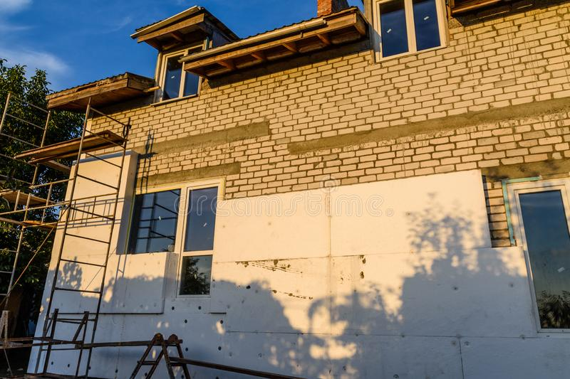 Insulation of the house with styrofoam. Scaffold on building stock image