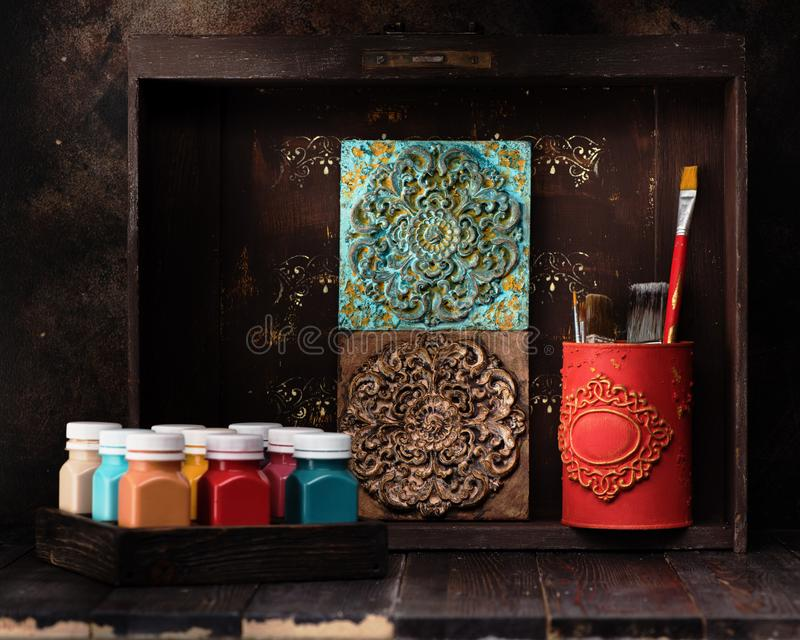Stucco molding plaster decorative ceramic tiles, Paints and paint brushes on a wooden shelf. Set for drawing and creativity stock photos