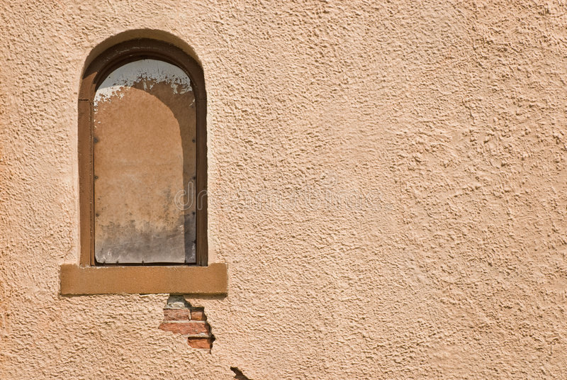 Stucco Wall. Brown stucco wall and arched window royalty free stock photo