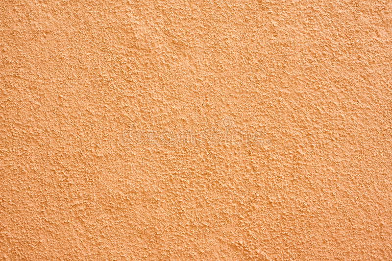 Stucco wall. Orange stucco textured wall background with natural light royalty free stock photography