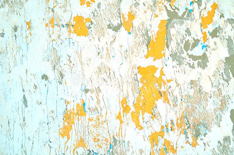 Textured stucco background - light beige peeling stucco and bright orange peeling paint. With blue streaks on the aged rough wall surface royalty free stock images