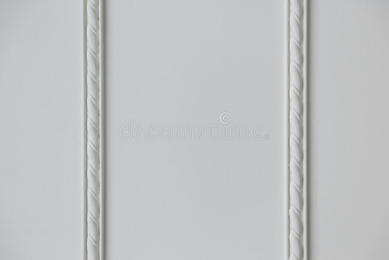 Two strips of stucco molding on a white wall. Two strips of embossed stucco molding on a white wall, close up royalty free stock images