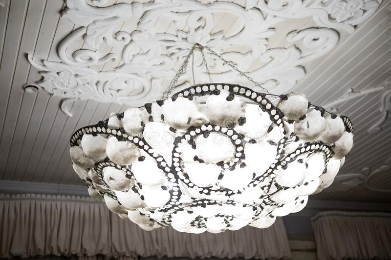Vintage chandelier hanging under white ceiling with stucco moldings.  stock photography