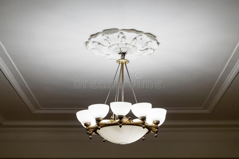 Vintage chandelier hanging under white ceiling with stucco moldings.  royalty free stock images