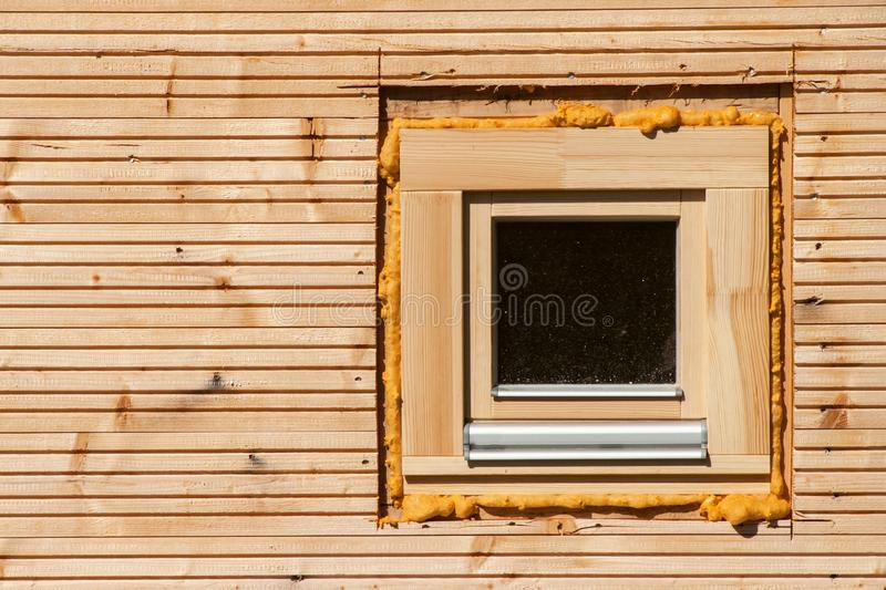 Wooden window. Foam window insulation on wooden construction. Building an eco-house. Heat insulation. stock photography