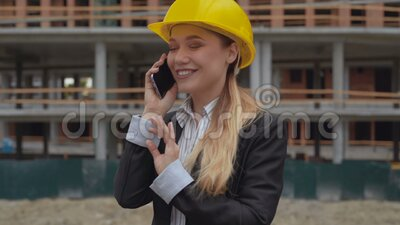 Female architect is excitedly and joyfully talking on the phone against the backdrop of a construction site. Woman in a stock video