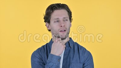 Tired young man waking up from nap on yellow background stock footage